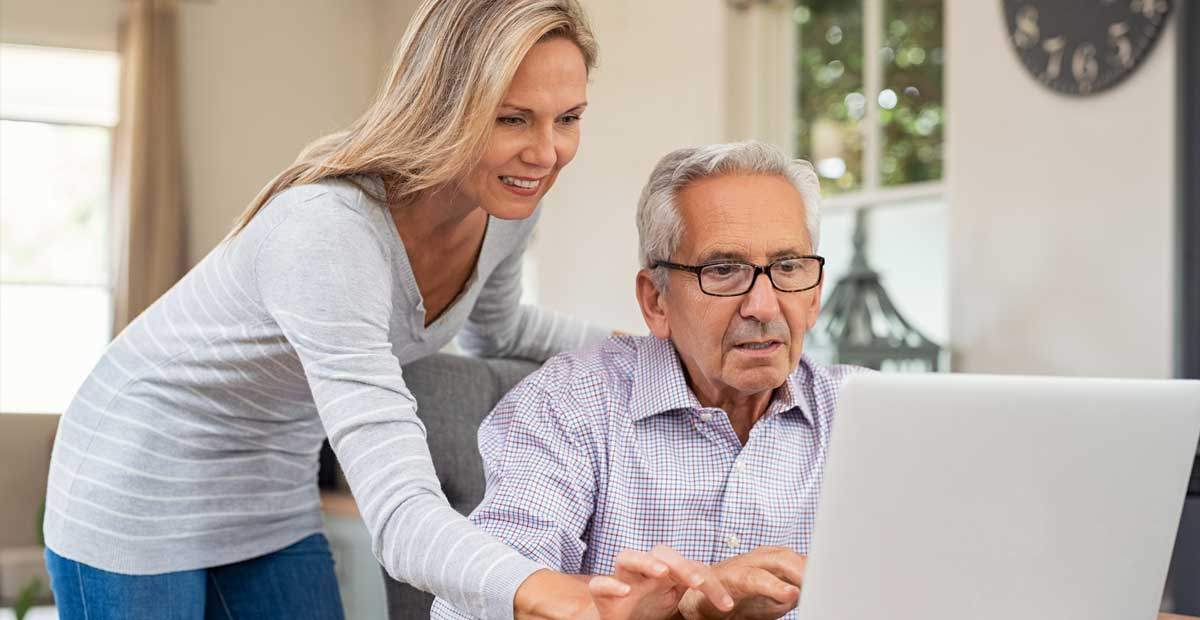 Woman helping older man with a laptop